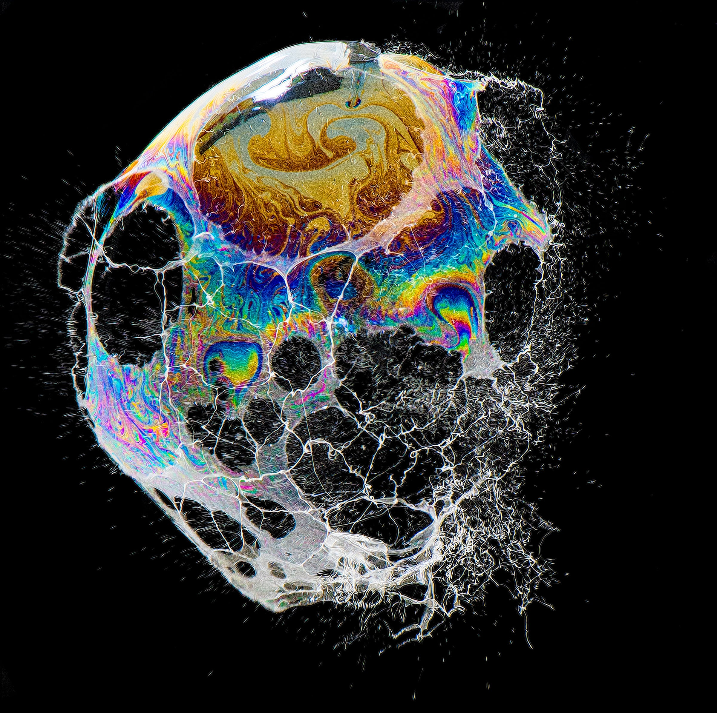 A colorful soap bubble in the process of bursting.