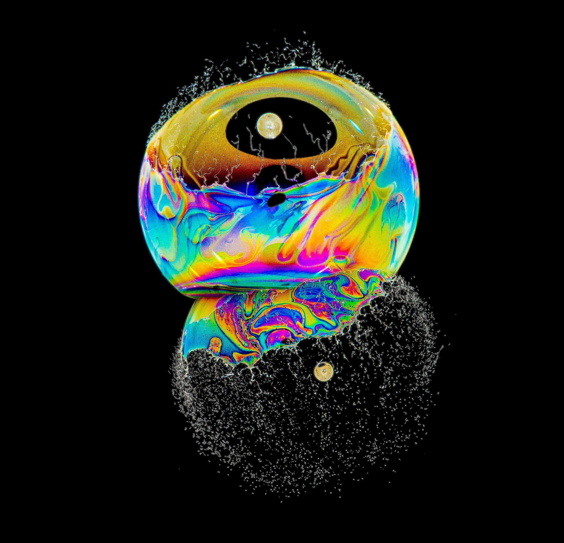 Two colorful soap bubbles bursts with a pellets and look as though they are reflected in glass.