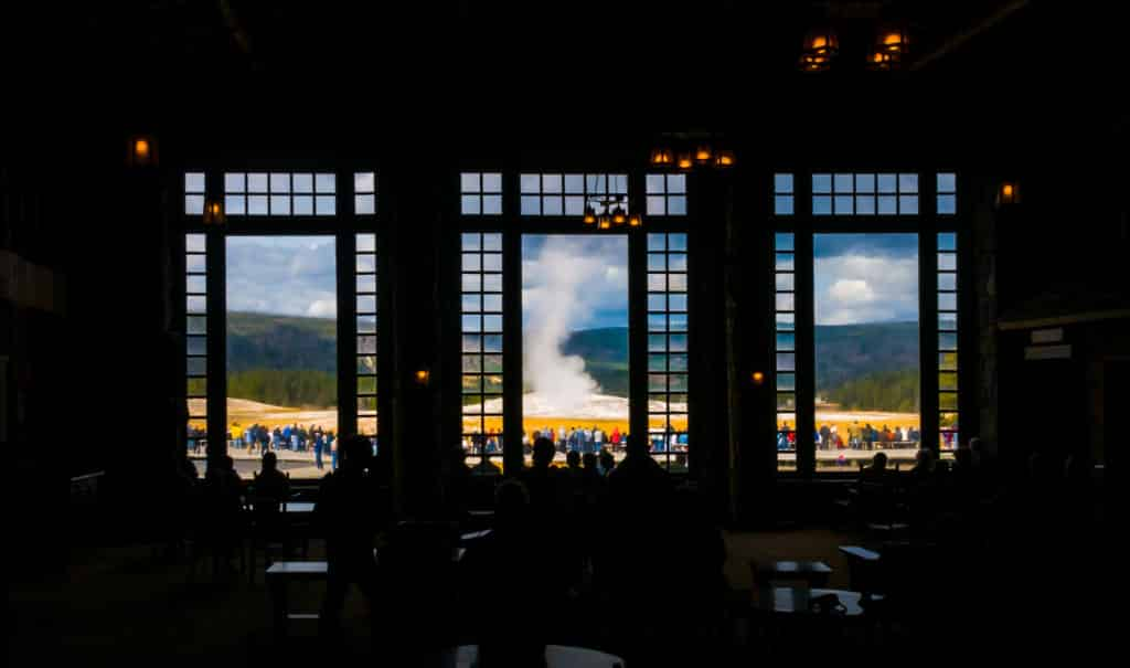 Visitors inside and outside the Old Faithful Lodge watch Old Faithful erupt.