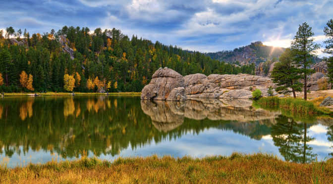 Clouds almost obscure the afternoon autumn sun as it highlights a granite rock formation and causes the multi-colored foliage to reflect in the still waters of Sylvan Lake in Custer State Park in South Dakota. Part of the Black Hills Landscapes article.