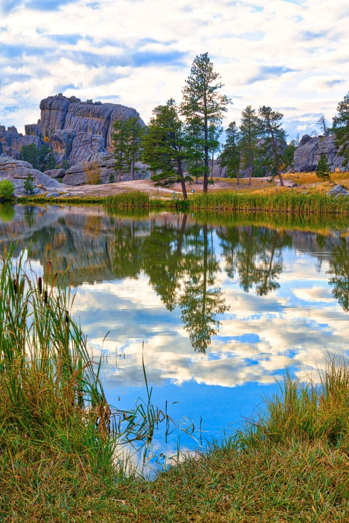 Clouds almost obscure the afternoon autumn sun as it highlights a granite rock formation and causes the multi-colored foliage to reflect in the still waters of Sylvan Lake in Custer State Park in South Dakota.