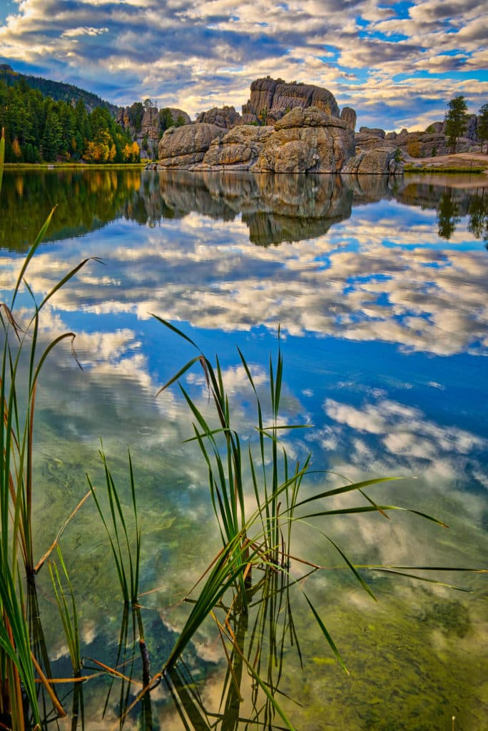 Afternoon clouds are reflected in the still waters of Sylvan Lake in Custer State Park near Custer, South Dakota.