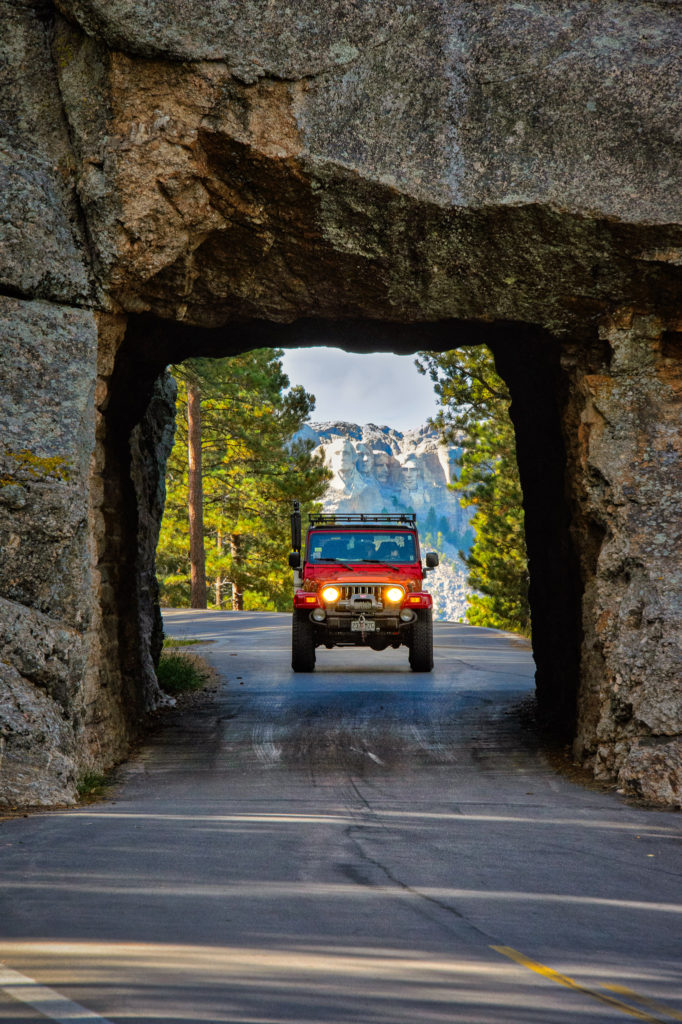 A red Jeep Wrangler enters a tunnel on the Iron Mountain Highway with Mount Rushmore visible in the distance.