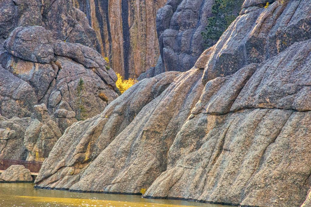 Golden leaves peek from behind granite formations at Sylvan Lake in Custer State Park, South Dakota.