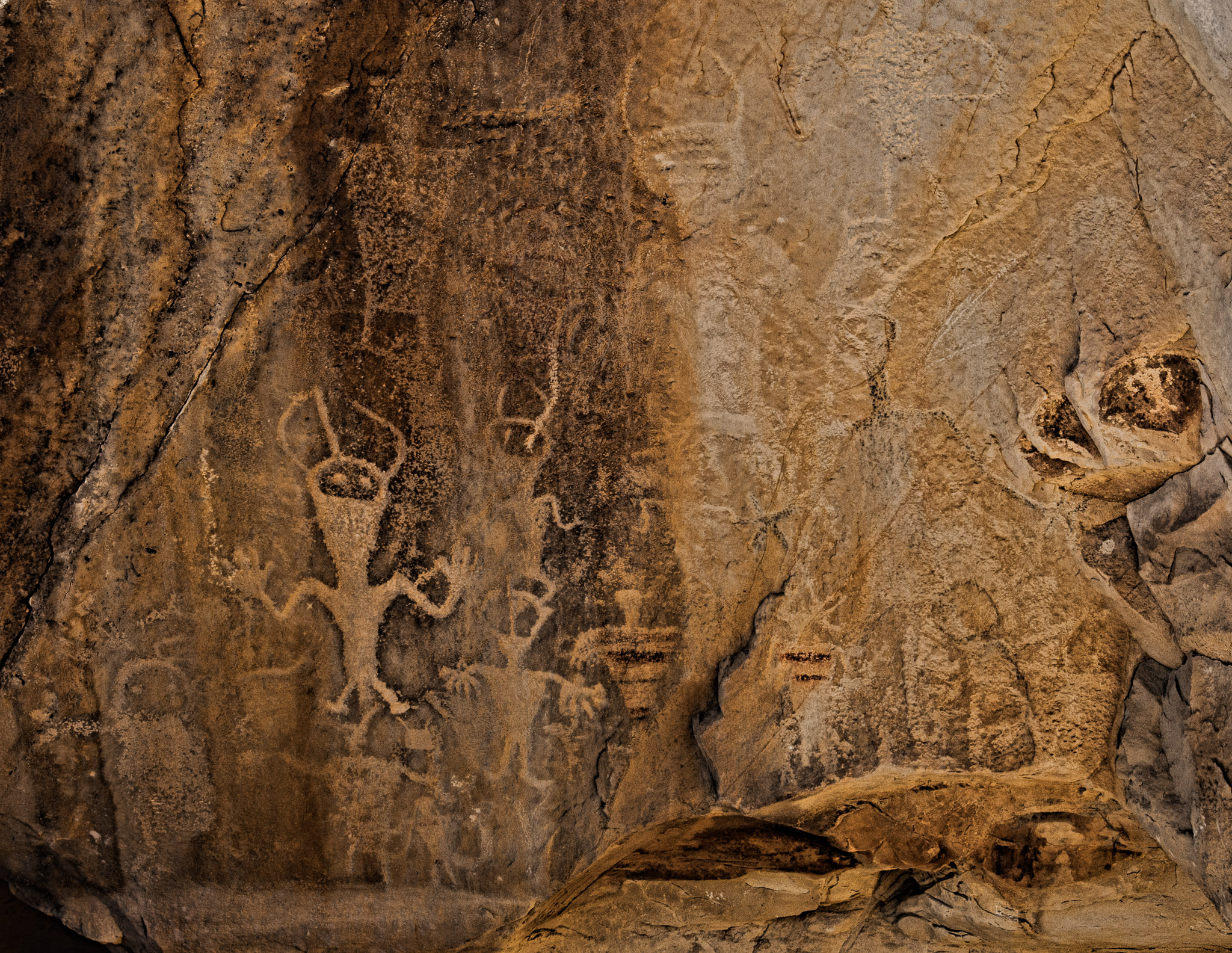 """Petroglyphs in """"Swelter Shelter"""" are thought to be from the Fremont Culture. Remnants of a red color can be discerned on the torsos of several of the figures. Swelter Shelter is located along Cub Creek Road in Dinosaur National Monument near Vernal Utah."""