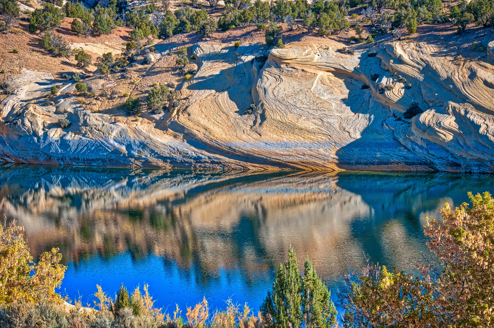 Petrified dunes of Weber Sandstone are reflected in Red Fleet reservoir on a fall day in Red Fleet State Park, north of Vernal, Utah.
