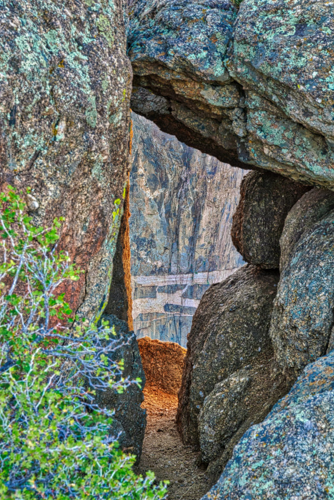 A view of the Painted Wall is nicely framed by boulders of ancient granite and schist. The scene is photographed from an overlook near the South Rim visitor's center in Black Canyon of the Gunnison National Park near Montrose, Colorado.