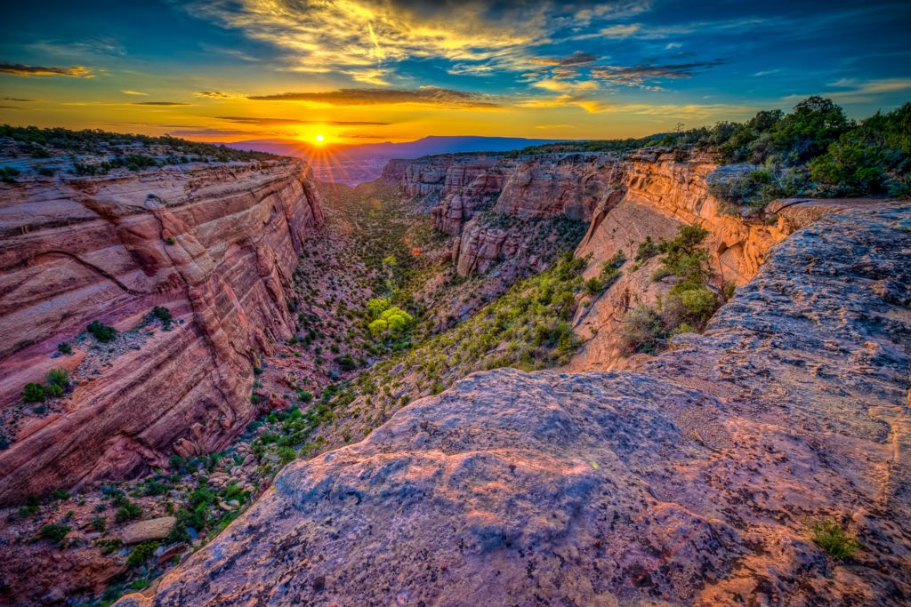 The sun rises over the city of Grand junction, Colorado, and lights up Red Canyon in Colorado National Monument.