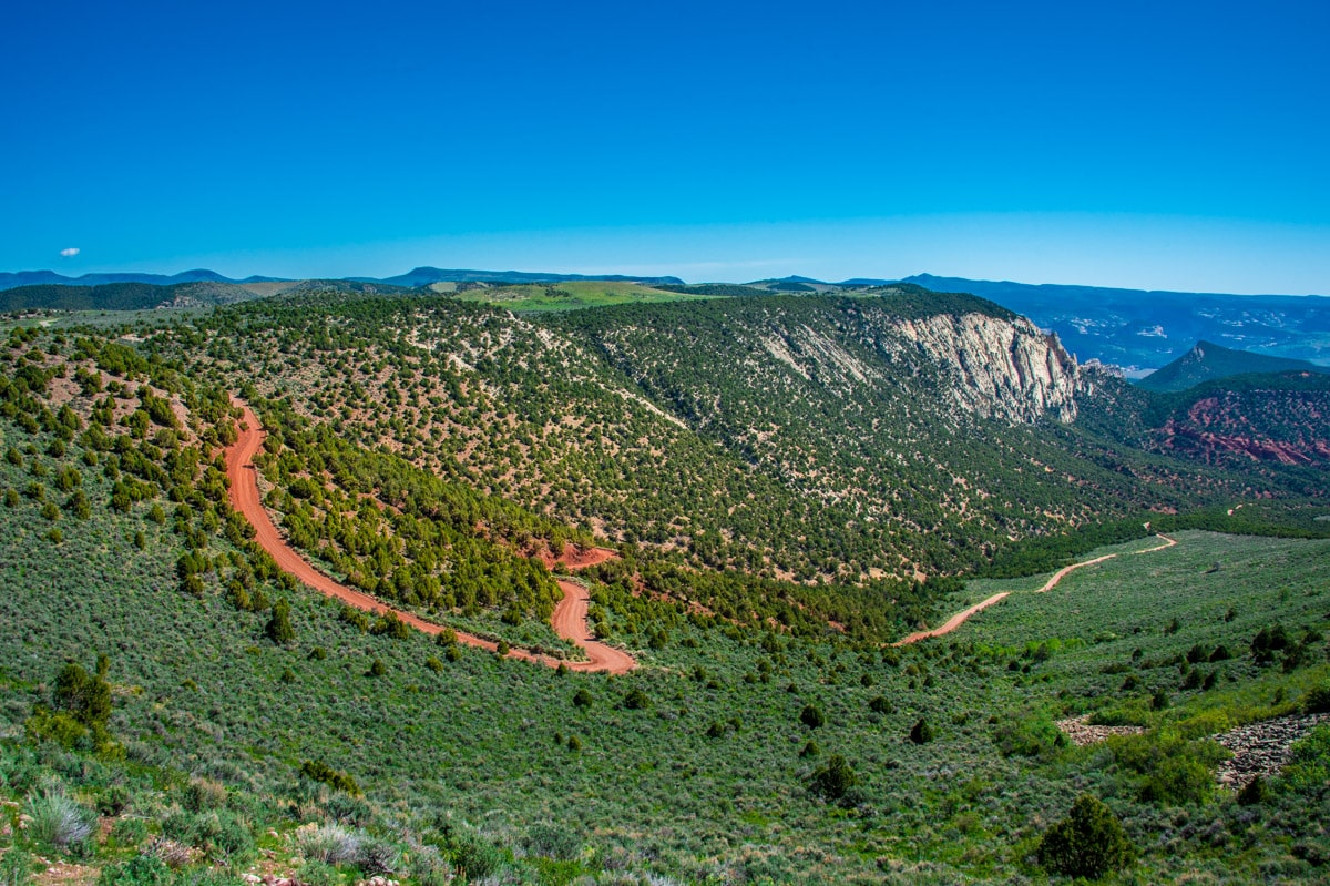 This view, taken from the Echo Park Overlook on the Harper's Corner Road, shows the zig-zag Dugway that leads down to the Echo Park Road, in Dinosaur National Monument, Colorado.. For all you geologists, you are seeing the Mitten Park Fault (heading away from you) and the Yampa Fault running in front of you.