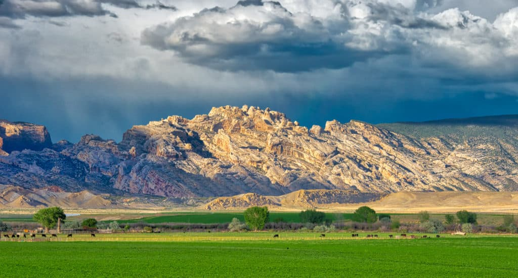 The dark rain clouds and virga serve as a backdrop to the magnificent Split Mountain and the ranch land in the foreground. This was taken along the entrance road to Dinosaur National Monument in Utah.