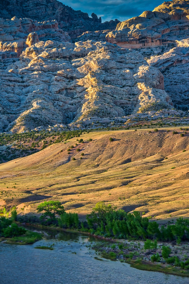 The Weber Sandstone of Split Mountain in Dinosaur National Monument catches the late afternoon sun. The Green River flows past in the foreground.