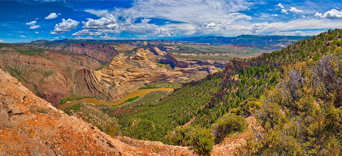 A panoramic view of the Mitten Park Fault along the Green River ib Dinosaur National Monument, Colorado. It showcases the interbedded sandstone and limestone layers of the Morgan formations up against the Weber Sandstone.