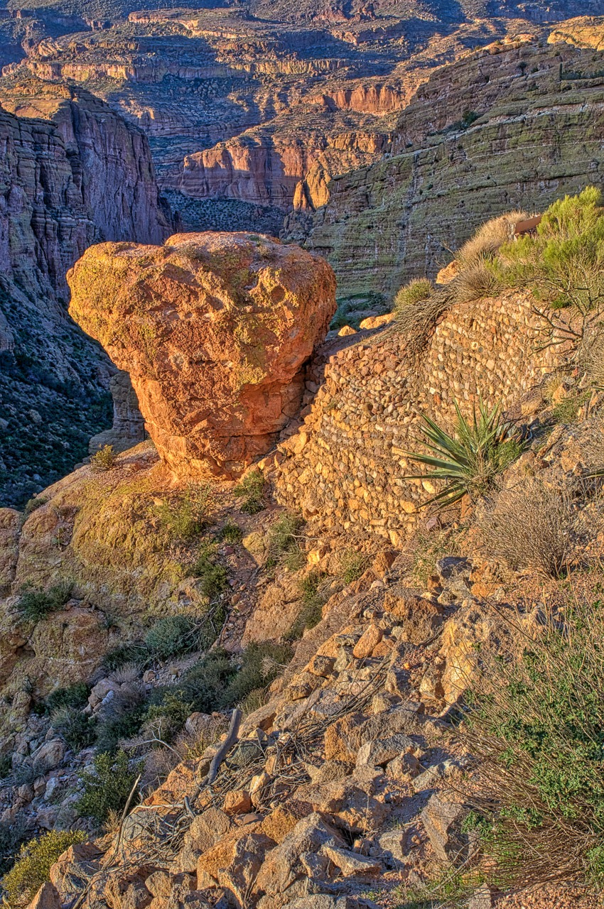 A view along the side of the Apache Trail showing a lone rock balanced upon a cliff, along with some erosion mitigation.