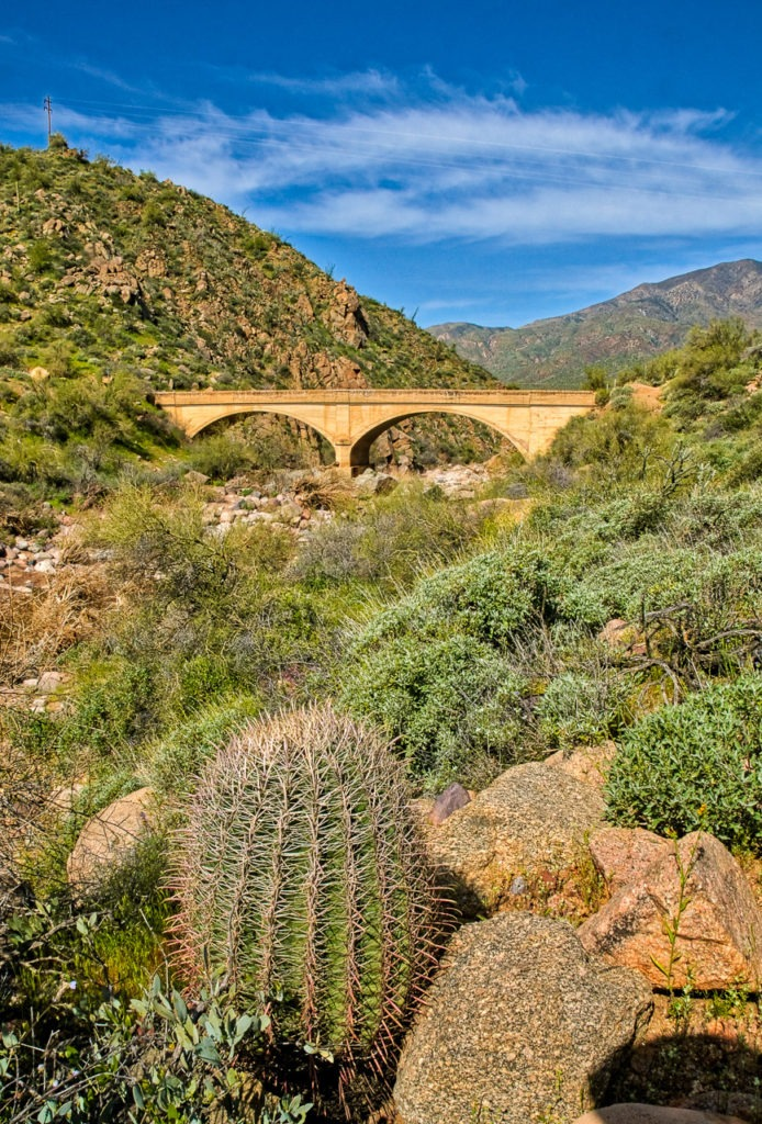 Just beyond a Fishhook Barrel Cactus is a double arch conrete bridge along the Apache Trail in Arizona.