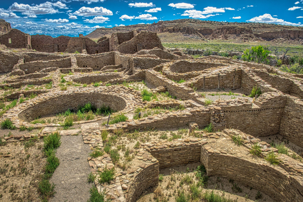 This interior view of Pueblo del Arroyo, in Chaco Canyon, New Mexico, shows several kivas, a multi-storied greathouse, and remnants of vigas.