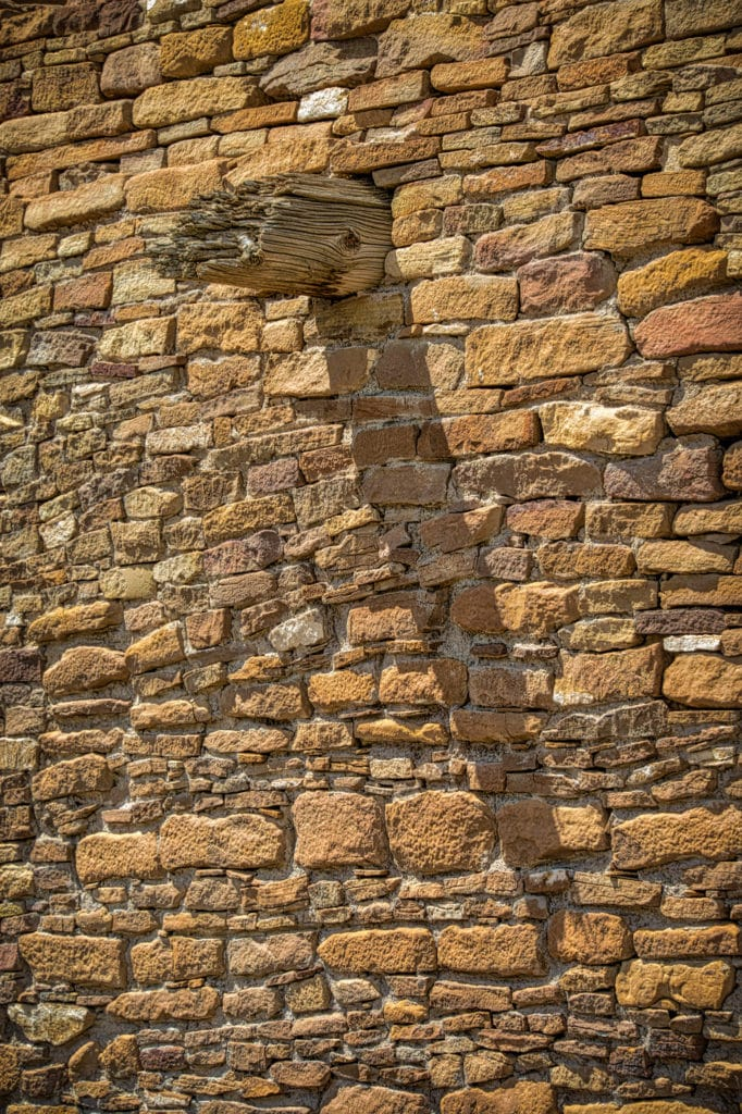 A protruding viga casts a shadow on a stone-veneered wall in Pueblo del Arroyo in Chaco Canyon, New Mexico.