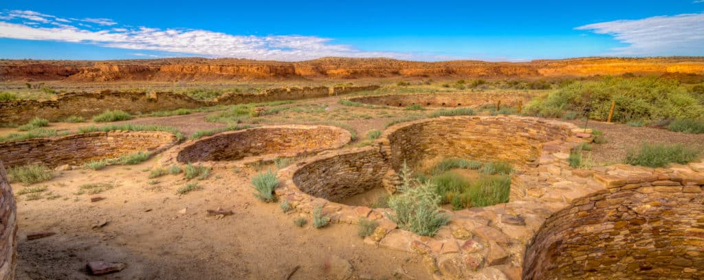 This panoramic view shows a cluster of kivas located in the northeast corner of Chetro Ketl's courtyard in Chaco Canyon, New Mexico. The large kiva in the distance is one of two great kivas at Chetro Ketl.