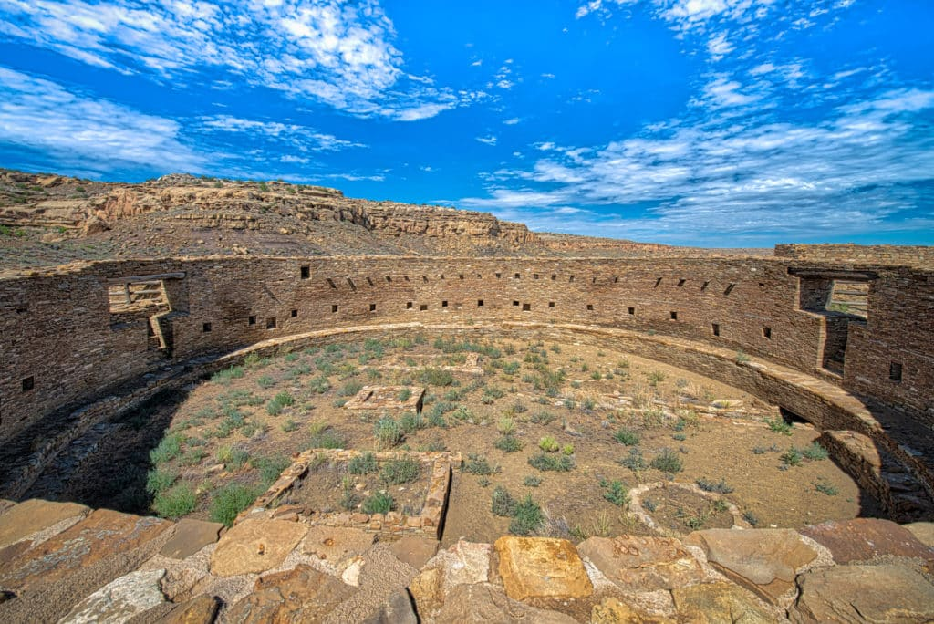 This is a view looking west across the interior of Casa Rinconada in Chaco Canyon, New Mexico. Casa Rinconada is the largest excavated great kiva at Chaco Canyon. The beams that appear at the north and south opening were placed there in 1933 as part of a restoration effort by the University of New Mexico.