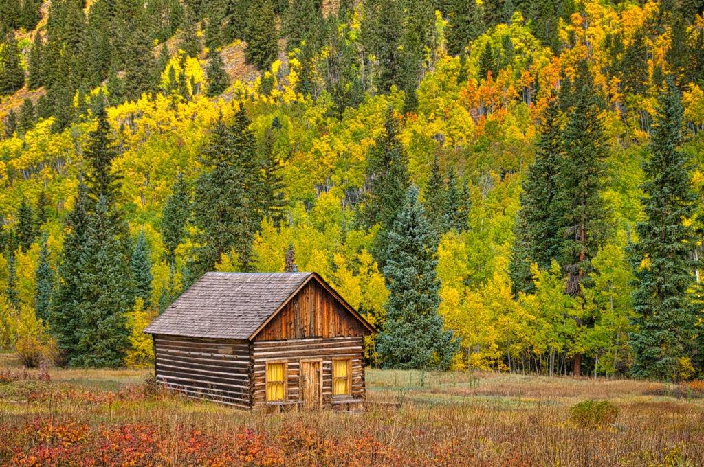 A sweet little log cabin sits in a field in Ashcroft Ghost Town near Aspen, Colorado.
