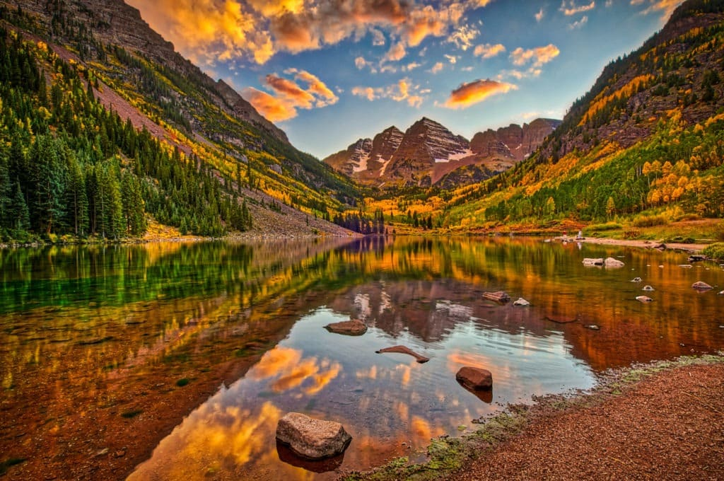 A colorful sunrise is reflected in the still waters of Maroon Lake in the Maroon Bells Recreation Arez near Aspen, Colorado.