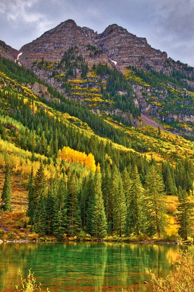 A typical fall afternoon in the Maroon Bells Recreations Area near Aspen, Colorado. The sun peeks through the gray clouds to illuminate the beautiful gold aspens.