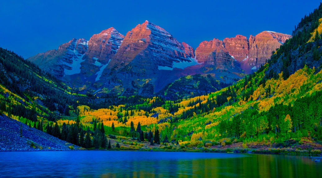 Warm morning light kisses the Maroon Bells just before dawn, near Aspen, Colorado.