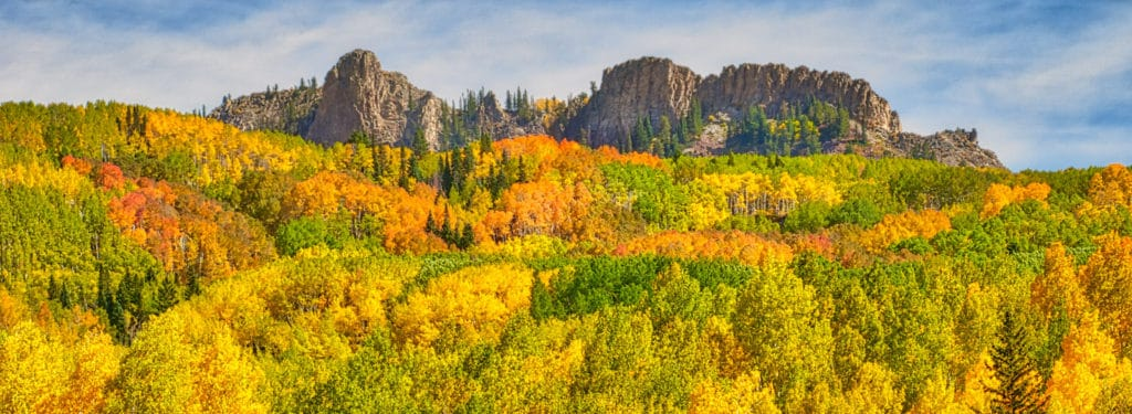 A panoramic view from CR12 southeast of Kebler Pass at a volcanic dike floating in a sea of aspens and fir.
