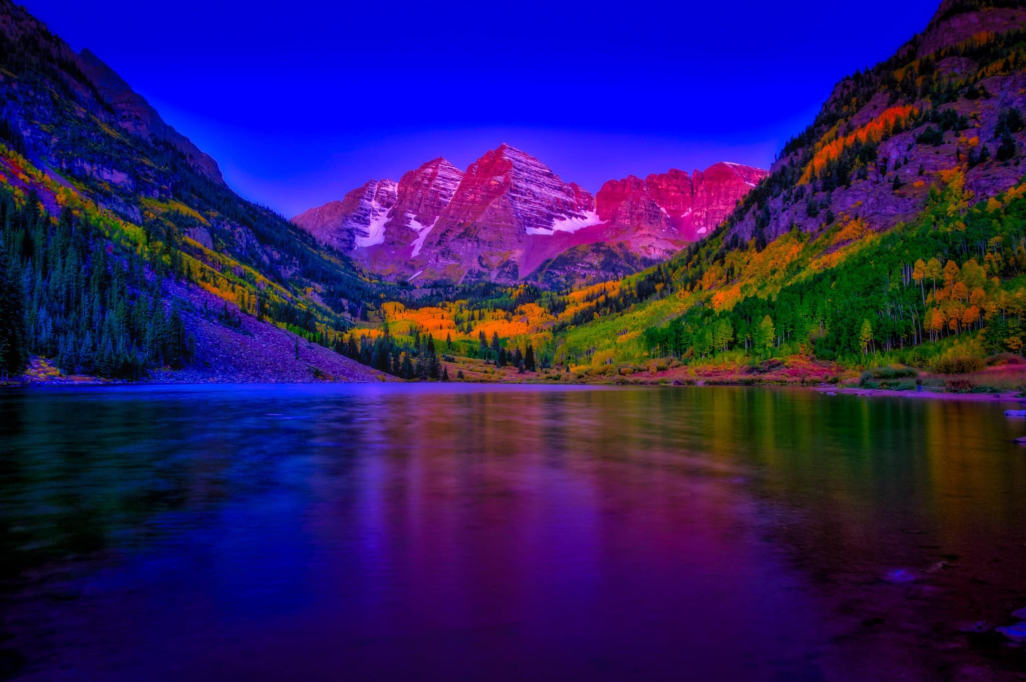 Magenta morning light kisses the Maroon Bells just before dawn in the Maroon Bells Recreation Area near Aspen, Colorado.