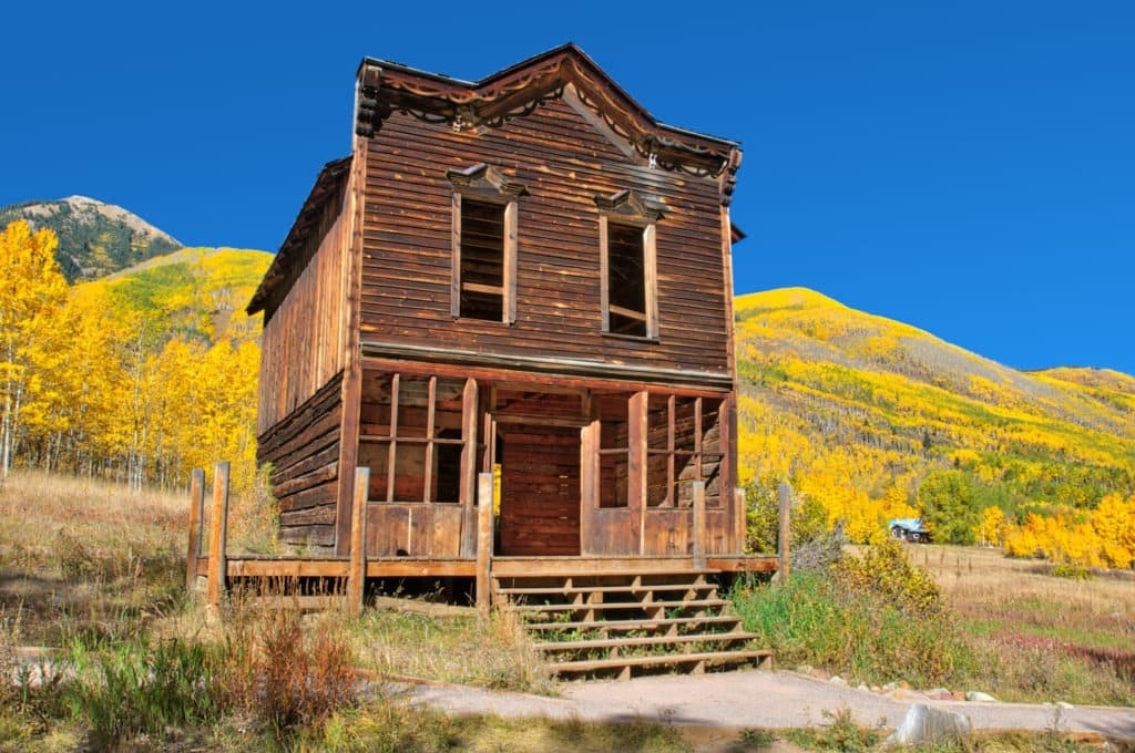 The remains of an old hotel with gingerbread along the roofline is on a street in Ashcroft Ghost Town near Aspen, Colorado.