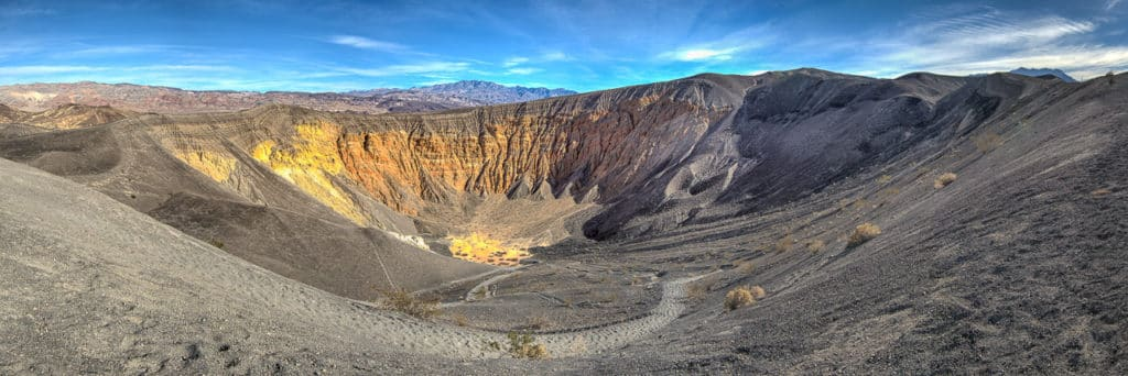 Ubehebe Crater is a maar volcano located off Scotty's Castle Road in Death Valley National Park, California. The colorful strata visible in the wall of the crater are sedementary deposits of the Navadu Formation. Ubehebe is the largest in a cluster of maar volcanoes located in this area. The explosions that formed these craters were caused by steam created when a small amount of basaltic magma encountered subsurface water.