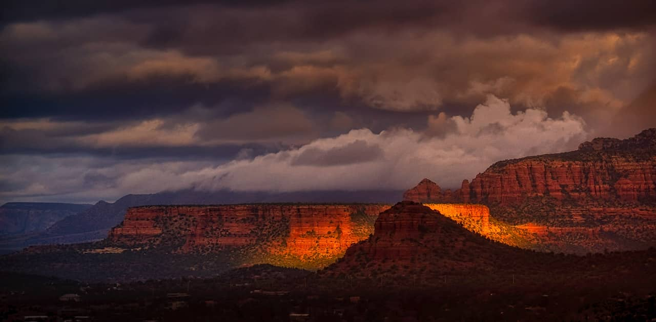 Beam of early-morning sunshine lights one butte while silhouetting another. North of Sedona, Arizona.