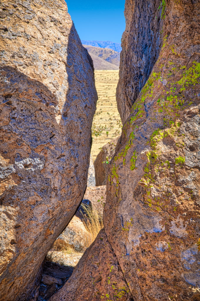 This slit in the rocks provides a view out across the pain to the mountains in the distance. Taken in City of Rocks State Park in southern New Mexico.