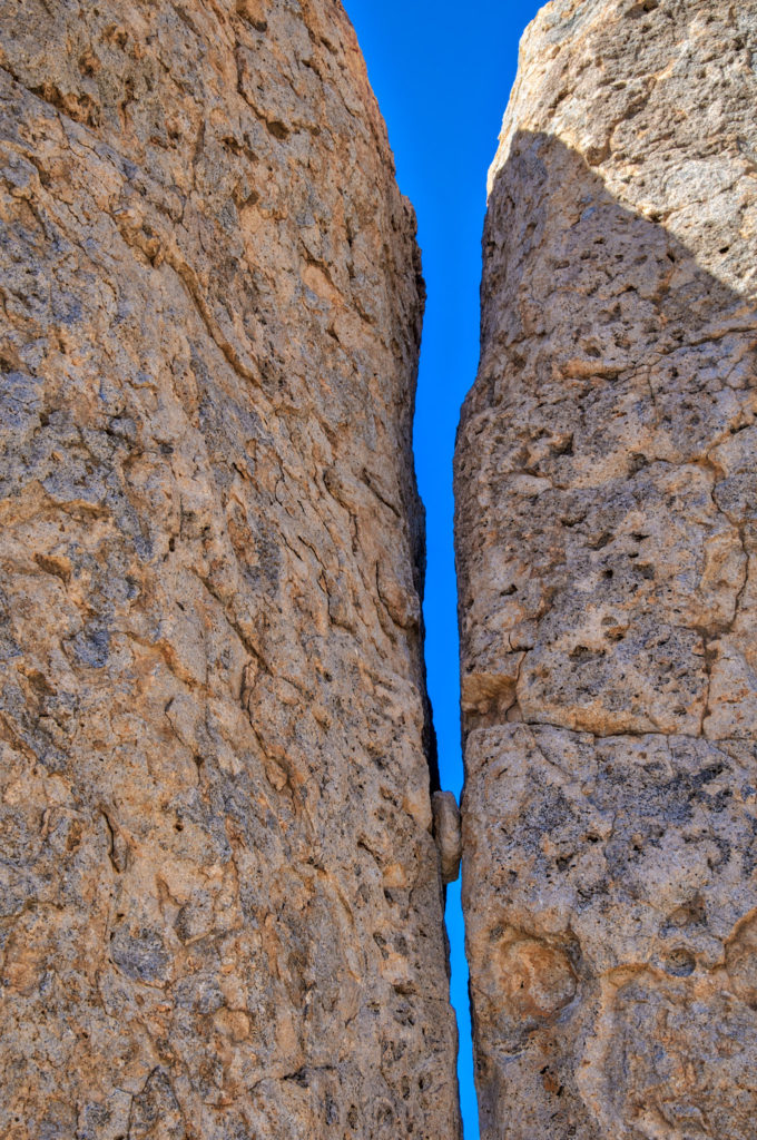 A piece of eroded rock is trapped in a crack between two pinnacles in City of Rocks State Park between Deming and Silver City, New Mexico.