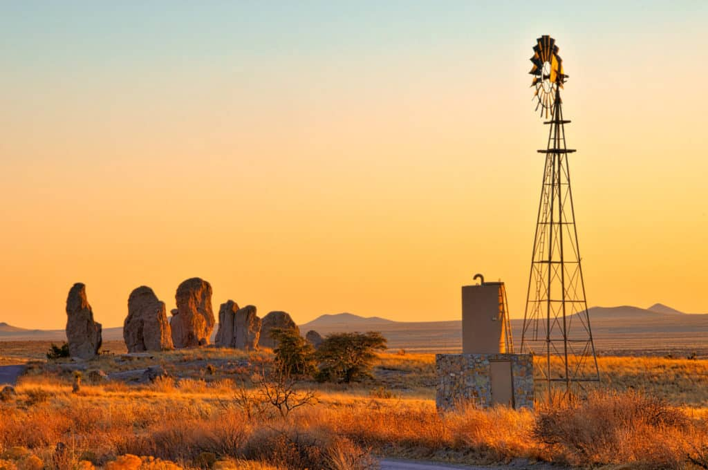 A windmill and water tank stand on the edge of City of Rocks at sunset.