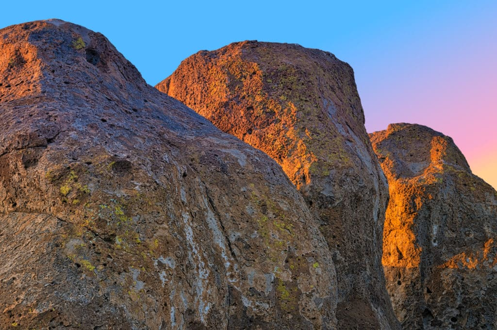 Alpenglow tinges the sky blue, pink, and yellow at sunset in City of Rocks State Park near Silver City, New Mexico.