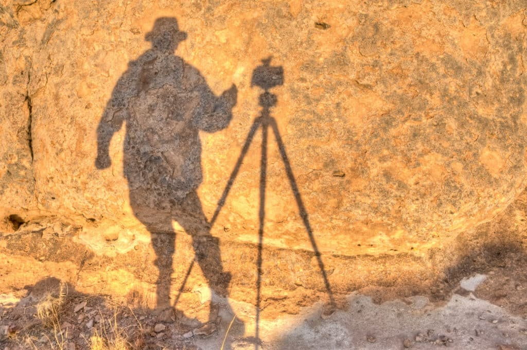 Sunrise shadow of the photographer, camera, and tripod on rock in City of Rocks State Park in New Mexico.