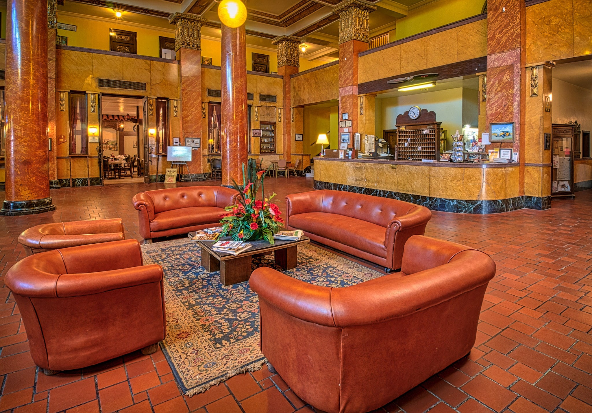 A view of the grand Gadsden Hotel lobby highlighting the leather furniture, tile floors, Italian marble, stained glass, and expansive grand staircase.