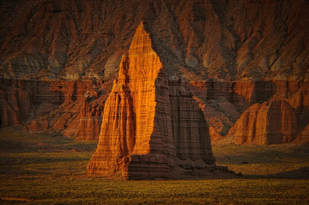 The summer dawn illuminates the face of the Temple of the Sun in Cathedral Valley, Capitol Reef National Park, Utah.