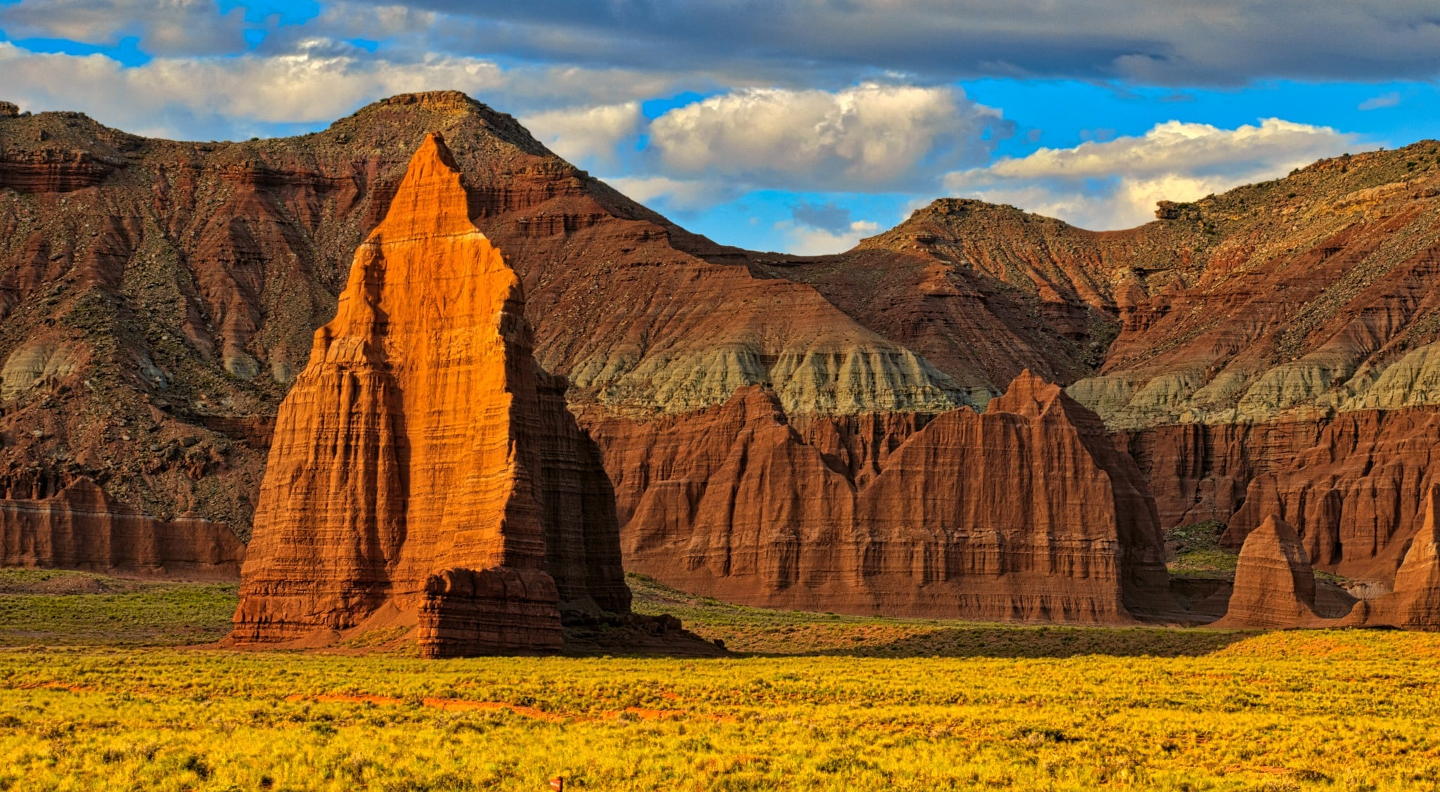The summer dawn illuminates the face of the Temple of the Sun and the surrounding cliffs in Cathedral Valley, Capitol Reef National Park, Utah.