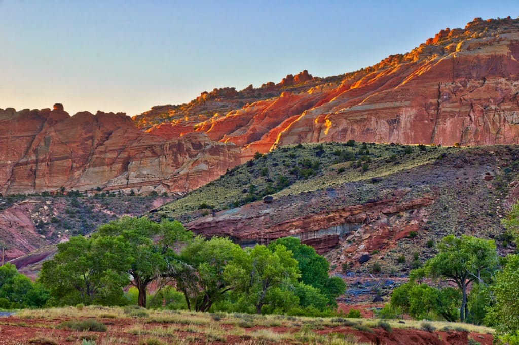The first light catches the edges of cliffs above Sulphur creek just upstream of its junction with the Fremont River in Capitol Reef National Park Utah.