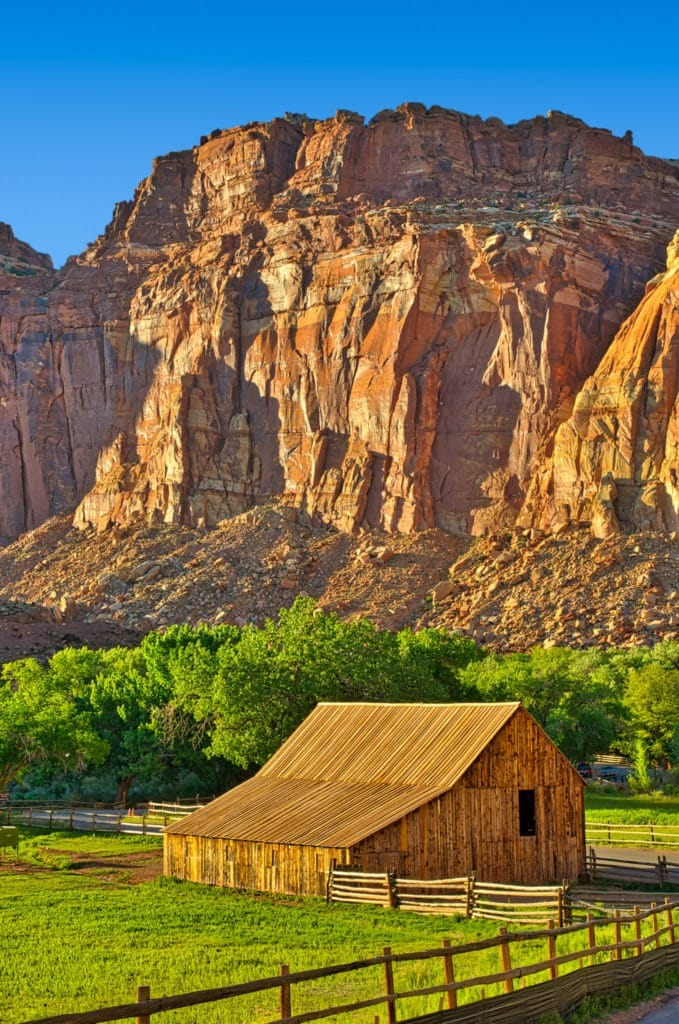 A view of one of the barns on the Gifford Homestead with red cliffs of the Waterpocket Fold in the background, in the Fruita District of Capitol Reef National Park in Utah.