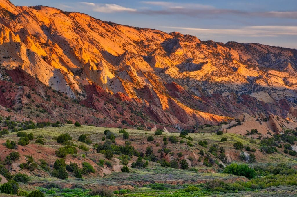 First light of day strikes the upturned rock layers of the Waterpocket Fold along the Notom-Bullfrog Road in Capitol Reef National Park, Utah.