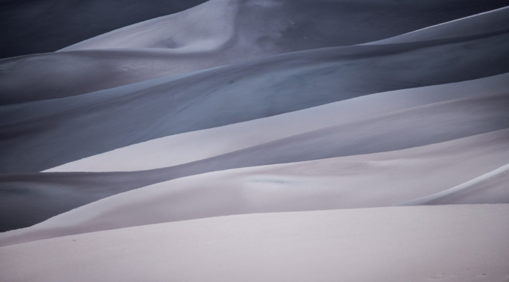 Partly cloudy skies cause interesting patterns of light and shadow on the sand dunes at Great Sand Dunes National Park and Preserve near Alamosa, Colorado.