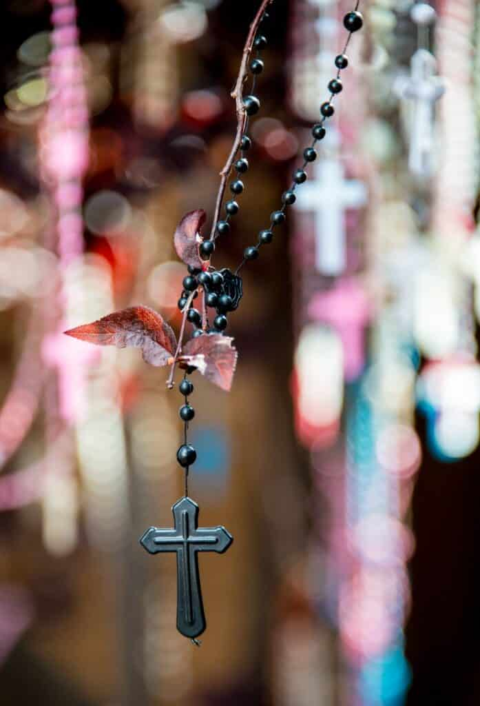 Visitors to the Loretto Chapel hang rosaries from flowering fruit trees that surround the chapel. Periodically, the rosaries are removed and buried beneath the chapel's windows. Soon, however, the trees are once again heavy with these devotions.