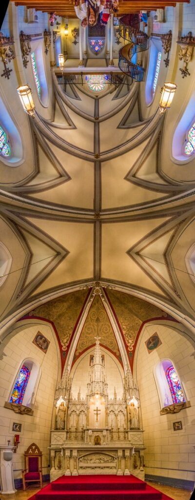 This panorama shows the complete ribbed vault of the Loretto Chapel from the high altar in the apse to the main entrance in the front. The chapel is located in Santa Fe, New Mexico.