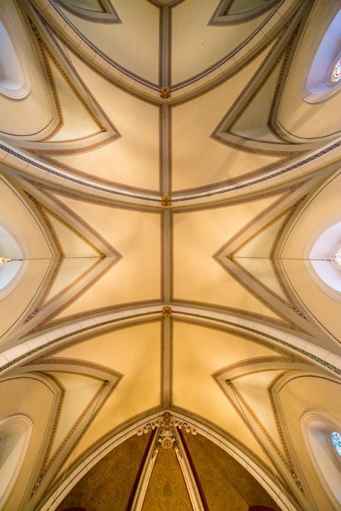 This is a view looking up at three of the quadripartite vaults in the ceiling of the Loretto Chapel in Santa Fe, New Mexico. Notive the different flower sculptures at the intersection of each main rib and the longitudinal ridge rib.
