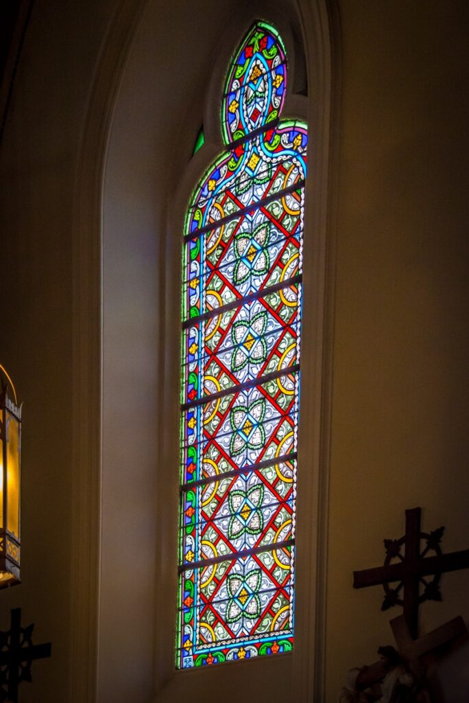 The style of the stained glass windows in the Loretto Chapel support the neo-Gothic architecture of this building.