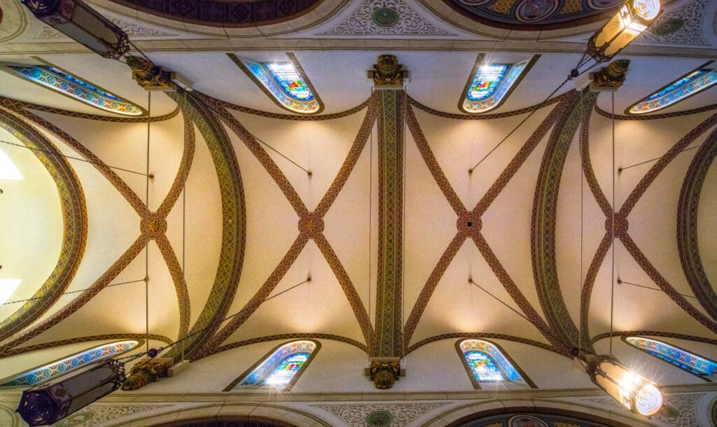 This view, looking up at the ribbed vault, showcases the beautiful stained glass clerestory windows, the richly decorated ribs, and the beautifully painted window casements.
