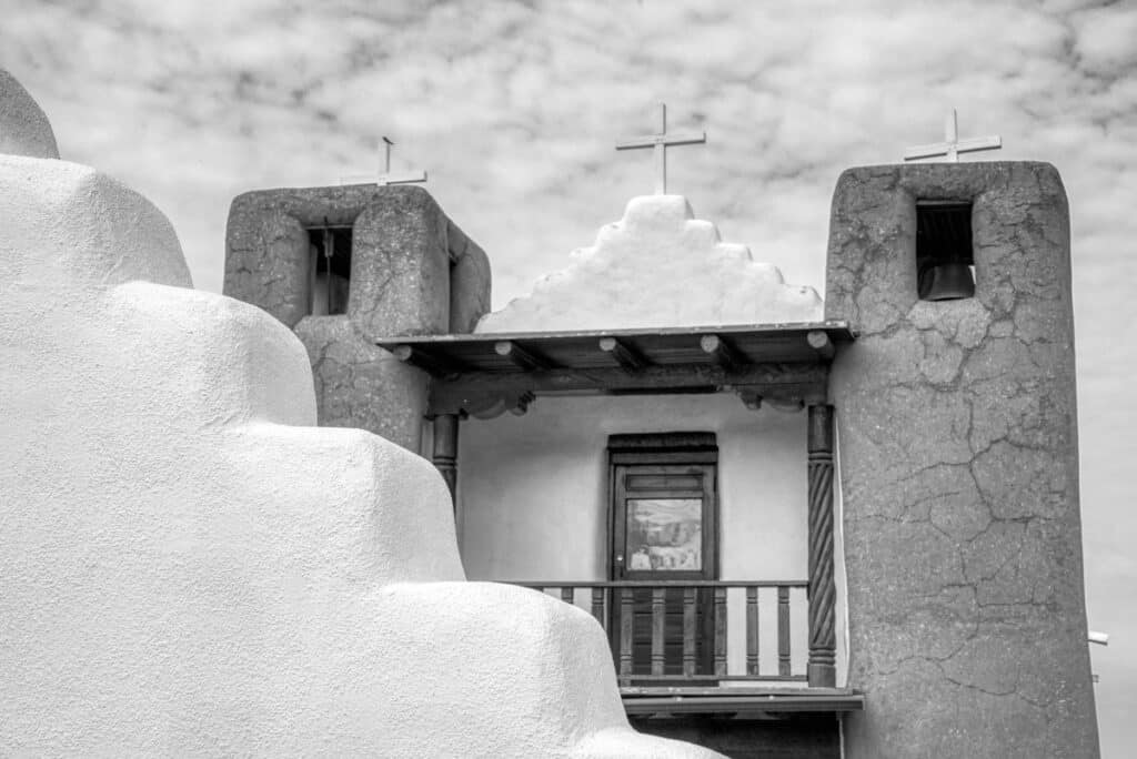 A black-and-white view of the balcony of St. Jerome Catholic Chapel with a portion of the arched gateway in front. The chapel is located in the heart of Taos Pueblo, New Mexico.