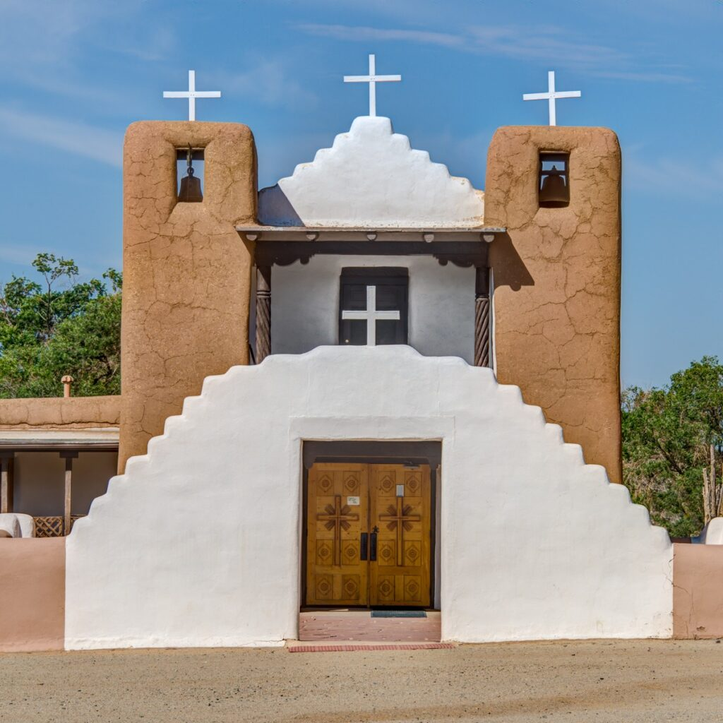 A frontal view of St. Jerome (San Geronimo) Catholic Chapel with the whitewashed arched gateway in front. The chapel is located in the heart of Taos Pueblo, New Mexico.